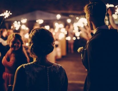 People holding sparklers in the night of an outdoor performance by a wedding band in Scotland